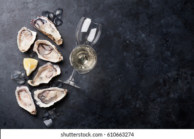 Opened oysters, ice and lemon with white wine over stone table. Half dozen. Top view with copy space