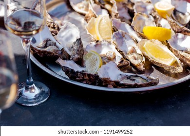 Opened oysters on a plate and wine glasses with sparkling wine on wooden table. Outdoor summer party.