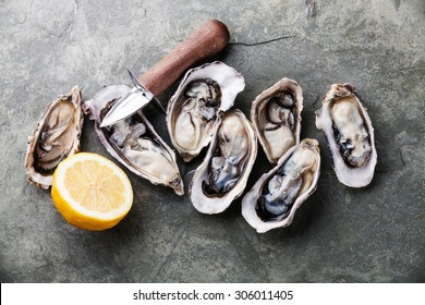 Opened Oysters on stone slate plate with lemon and oyster knife