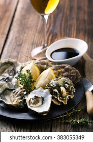 Opened Oysters in the shell with a lemon and a glass of wine on a plate on a wooden background