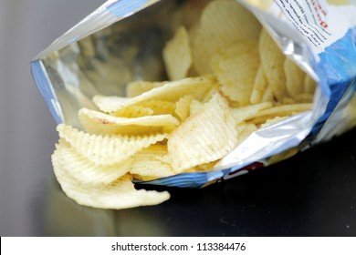 Opened pack of delicious spicy potato chips over black  table. Open bag with potato chips. Potato chips in bag on reflecting background