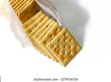 Opened package of saltine crackers also known as soup and soda crackers over white, not isolated.
