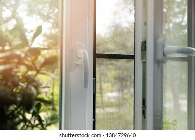opened plastic pvc window with mosquito net wire screen installed
