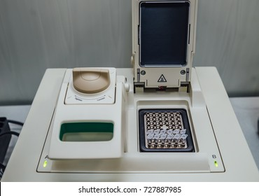 Opened polymerase chain reaction (PCR)  cycler machine with DNA samples