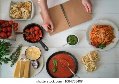 Opened recipe book in the hands of woman in front of a table with utensils and fresh vegetables. A homemaker cooking while following the instructions of a cookbook. Space for your text. Healthy food.
