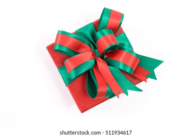 Opened red Christmas gift box with green bow and ribbon on the white background.
