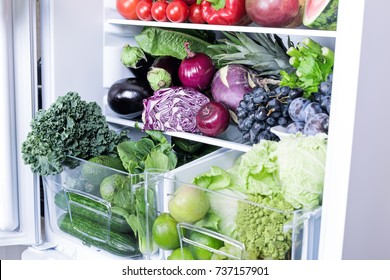 Opened refrigerator full of vegetarian healthy food, vibrant colour vegetables and fruits inside on fridge
