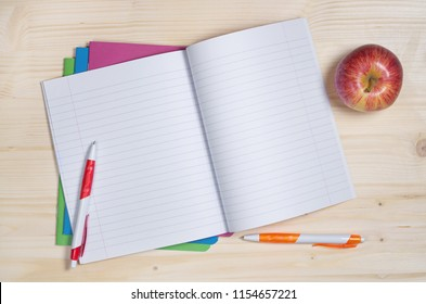 Opened school notebook with pens and apple on the wooden desk. Top view with empty place for text
