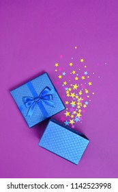 Opened shiny classic blue gift box with satin bow and magic confetti in the shape of stars as attributes of party on purple background