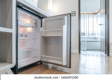 opened small refrigerator under the counter and in front of toilet in delux room at resort and hotel.