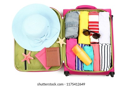Opened suitcase with clothes, sunglasses, passports and sunscreen bottle on white background