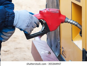 Opened tank and gun of gas station. Fuelling gasoline in car.