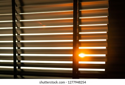 Opened venetian plastic blinds with sunlight in the morning. White plastic window with blinds. Interior design of living room with window horizontal blinds. Window slatted shades made of plastic.