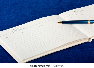 Opened wedding guest book with a pen on a blue background