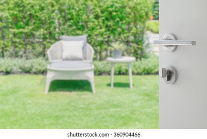 opened white door to blurred white bench in the garden as background