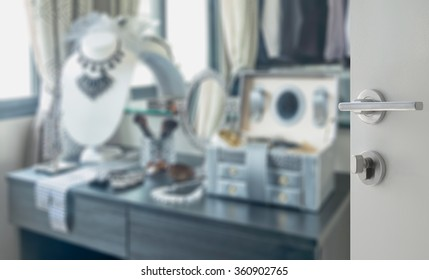 opened white door to blurred wooden dressing table with accessories at home