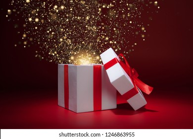 Opened white gift box on red background