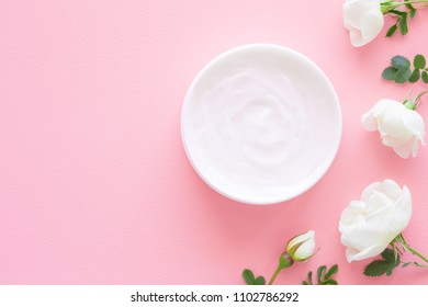 Opened white jar of natural herbal cream for women on pastel pink table. Beautiful white roses. Fresh flowers. Care about clean and soft face, hands, legs and body skin. Empty place for text.