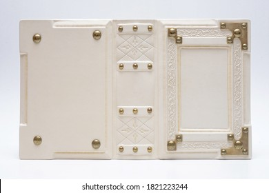 Opened white leather book cover with embossed leather and metal corners