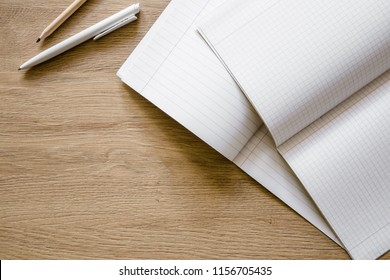Opened white squared and lined exercise books with pen and pencil on the wooden work table. Empty place for text. Top view. Flat lay.