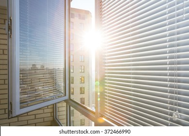 Opened window on sunny day with horizontal plastic blinds