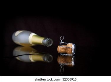 Opened wine bottle lays on a table. From her champagne flows