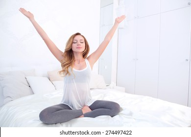 Opened to world. Pretty meditating woman sitting in lotus pose and holding arms out