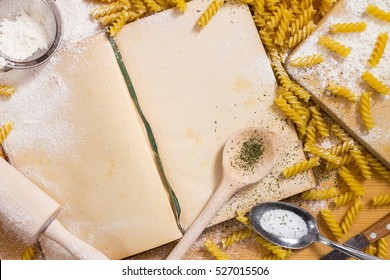Opened yellowed cookbook with blank pages, cooking spoon and rolling pin, pasta and flour on wooden background - still life with copy space