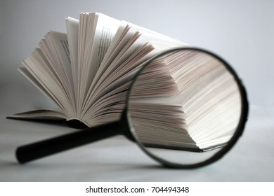 Opening book macro with magnifying glass on a white background
