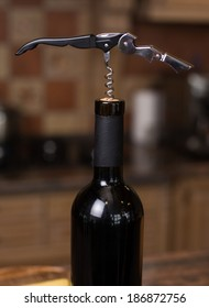 Opening a bottle of wine with corkscrew in the kitchen
