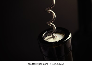 Opening bottle of wine with corkscrew on dark background, closeup