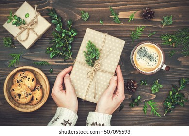 Opening Christmas present. Woman's hands holding decorated gift box on rustic wooden table. Ideal Christmas morning. Overhead, flat lay, top view