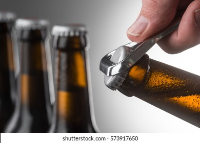 Opening cold bottle of beer using a metal opener. Three more unopened bottles over grey wall in unfocused background.