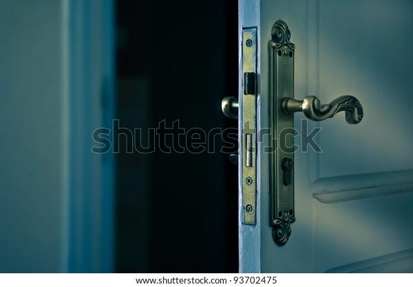 An opening door to a darker room
