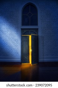 Opening door with yellow glow in the church at night