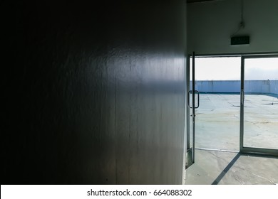 Opening emergency exit door in a dark room with light outside
