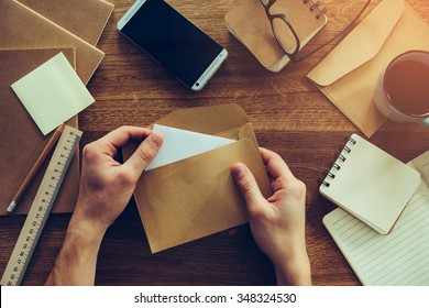 Opening envelope. Close-up top view of male hands opening envelope over wooden desk with different chancellery stuff laying on it