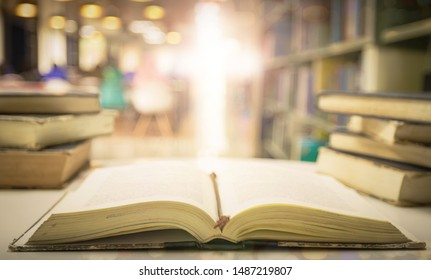 Opening holy bible with blurred cross background