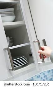 Opening kitchen cabinet door, focus on hand opening action