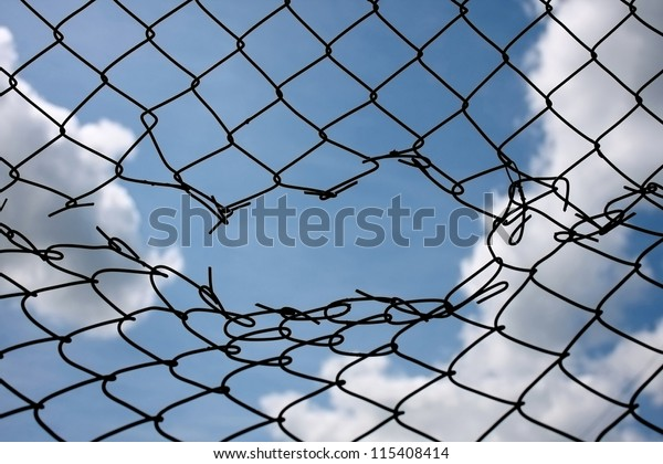 Opening in metallic fence against a blue sky with white clouds. Challenge / uncertainty / breakthrough concept / metaphor. Chain-link, wire netting, wire-mesh, cyclone hurricane fence.  Happy - sad,