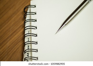 an opening notebook with a pencil placed on it