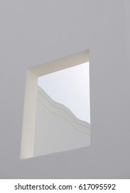 Opening in a white facade showing part of roof line and sky, all in shades of white
