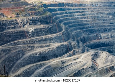 Open-pit mining raw minerals for steel production. Giant iron ore quarry in Rudny, Kazakhstan. Yellow quarry truck down. Quarry steps under beauty sun.