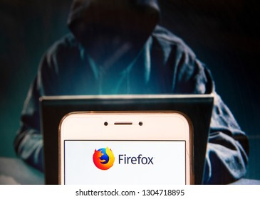 Open-source web browser developed by Mozilla Foundation, Firefox, logo is seen on an Android mobile device with a figure of hacker in the background.