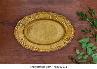Openwork oval plate,  eucalyptus twig, top view on rustic brown wooden background.