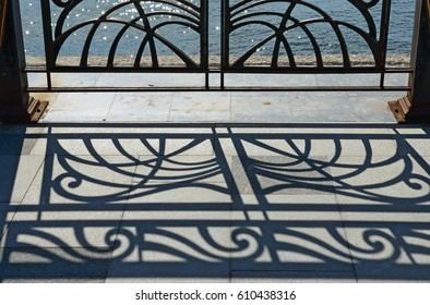 Openwork silhouette and shadow of forged iron railing in bright contre-jour sunlight on embankment in Sudak, Crimea, Russia.