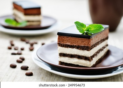 Opera cake on a light brown background. tinting. selective focus