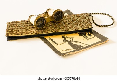 Opera glasses, handbag and playbill on a white background.