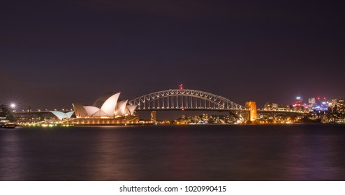 opera house and harbour bridge in Sydney at night, reflection on harbour view from Botanic garden. It is illuminated by golden lights at night to attract tourists. Australia : 04/02/18