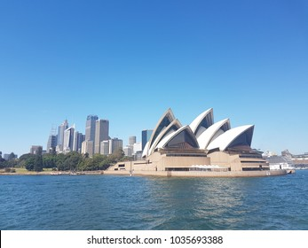 Opera house, Sydney, Australia on 14 December, 2017. It's an Opera house by the sea infront of it and big blue sky and sea in the background. It is a landmark of Sydney.
